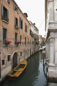 Canal with boat and buildings in Venice, Italy.