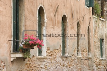 Arched windows and geranium flowers in Venice, Italy.