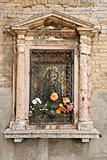 Religious shrine on exterior of building in Venice, Italy.