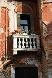 Worn building with balcony and flowers in Venice, Italy.