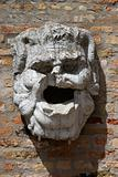 Concrete head hanging from brick wall.