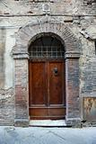 Wooden door with brick archway.