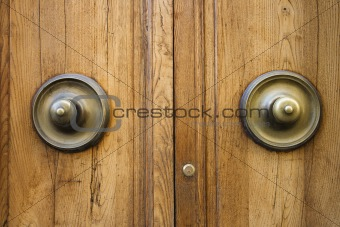 Brass doorknobs on wooden door.