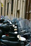 Row of motorcycles beside building.