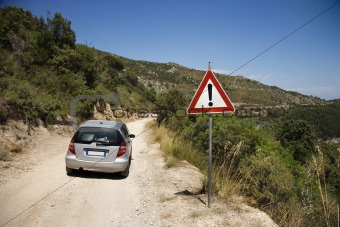 Car heading down dirt road with caution sign.