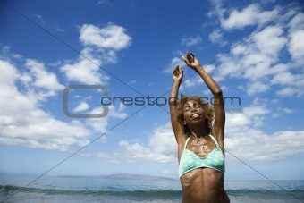 Woman stretching arms with ocean in background.