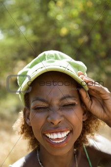 Woman smiling with hand on cap and squinted eyes.