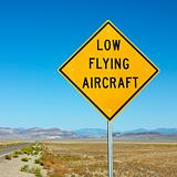 Low flying aircraft sign on side of highway.
