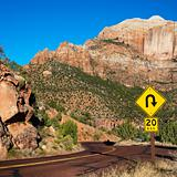 Curve caution sign on road winding through desert of Zion Nation
