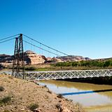 Suspension bridge over river with rock cliffs in Utah.