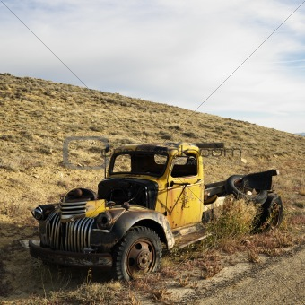 Old yellow pickup abandoned on hill.