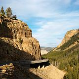 Highway winding through steep Wyoming mountains.