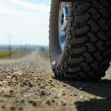 Big truck tire on gravel road.