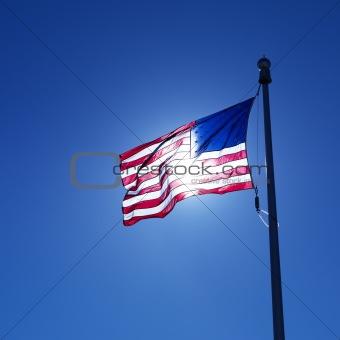 Waving American flag backlit by sun.
