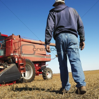 Farmer walking toward combine.