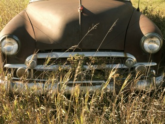 Old abandoned antique car in field.