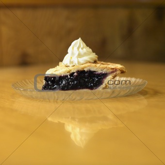 Slice of blueberry pie on plate with whipped topping.