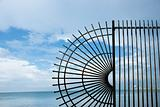 Wrought iron fence at edge of sea.