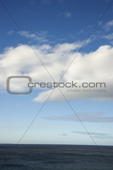Blue sky and clouds over ocean.