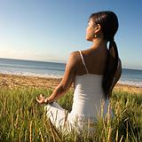 Woman sitting on beach and meditating.