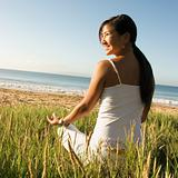 Woman sitting on beach meditating.