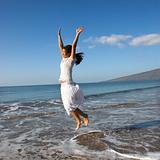 Woman jumping in air at the shoreline.