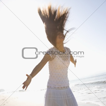 Woman with arms outward and throwing hair back.