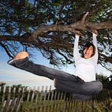 Woman holding on to tree and kicking air.