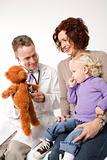 Doctor using teddy bear to demonstrate stethoscope to little gir