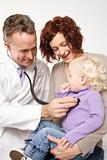 Mother holding her daughter while doctor uses stethoscope.