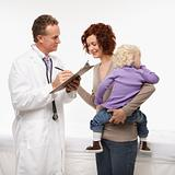 Doctor taking medical history while mother holds her daughter.