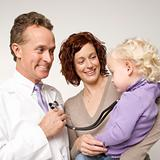 Doctor holding stethoscope as little girl looks on.