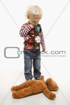 Female toddler looking at her teddy bear on ground.