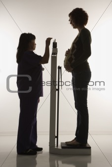 Pregnant woman being weighed.