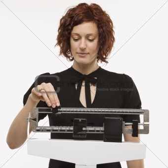 Pregnant woman checking her weight.