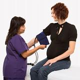 Pregnant woman having blood pressure checked.