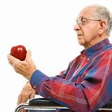 Elderly man holding apple.