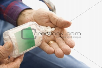 Man pouring pills into hand.