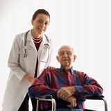 Doctor with hands on elderly man's shoulder in wheelchair.