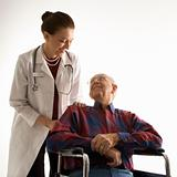 Doctor looking at an elderly man in wheelchair.