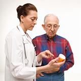 Doctor pointing at prescription bottle as elderly man looks at b