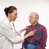 Doctor listening  to elderly man's heart with stethoscope.