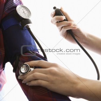 Close-up of woman taking blood pressure of a man.