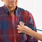 Female hand with stethoscope at elderly man's chest.