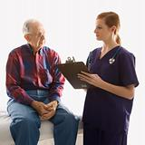 Female in scrubs taking notes from elderly man.