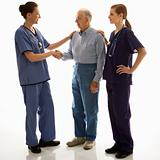 Woman in scrubs shaking hand of elderly man with another woman h