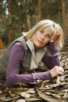 Caucasian woman lying in forest.
