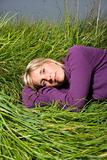 Caucasian woman lying in grass.