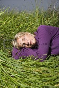 Caucasian woman lying in grass.