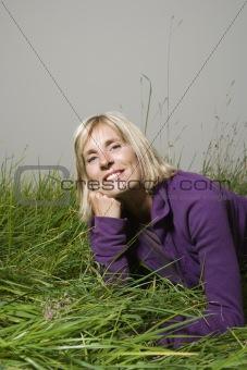 Caucasian woman lying in field.